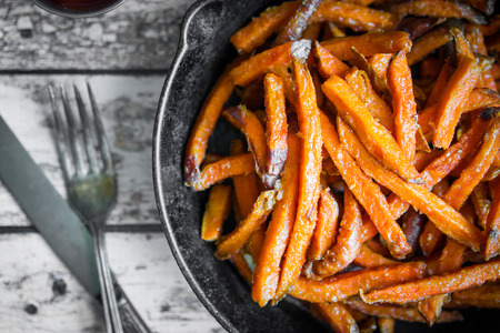 Sweet potato fries in cast iron skillet on wooden background Zdjęcie Seryjne - 45599545