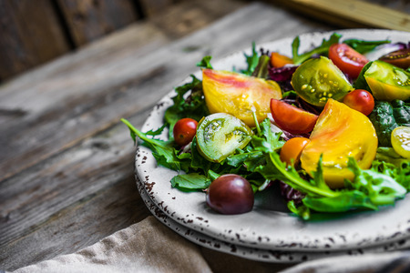 Fresh salad with spinach,arugula and heirloom tomatoes on rustic background Stock Photo