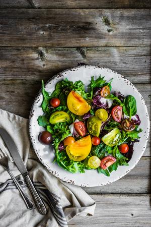 ensalada tomate: Ensalada fresca con espinacas, rúcula y tomates en el fondo de la herencia rústico