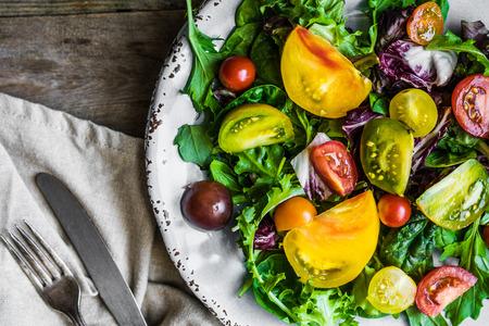 tomate: Salade fraîche aux épinards, roquette et tomates Heirloom sur fond rustique