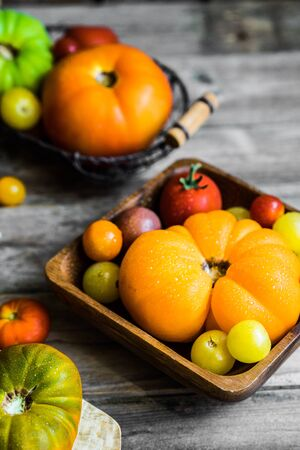 Colorful heirloom tomatoes on rustic wooden background