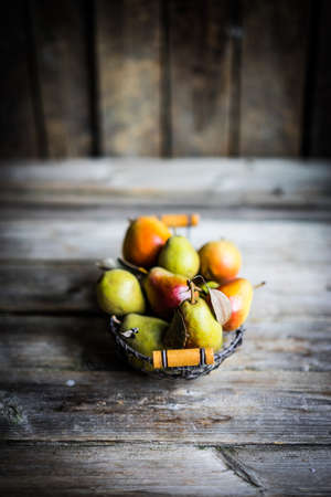 fruits in a basket: Autumn pears on rustic wooden background Stock Photo