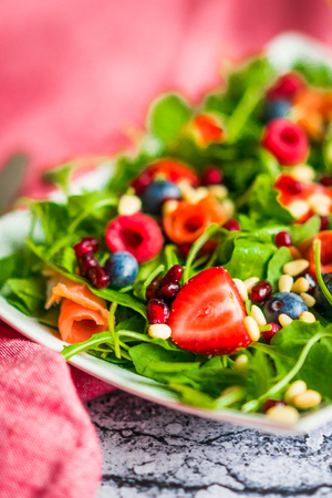 fruit plate: Healthy salad with arugula,spinach,smoked salmon and berries Stock Photo
