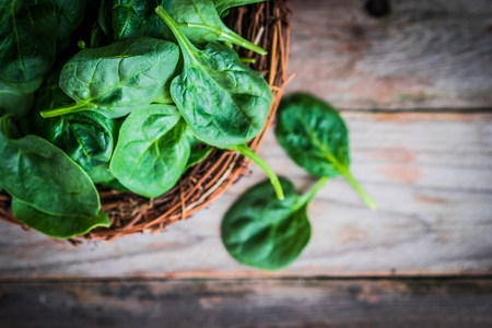 natural backgrounds: Fresh spinach on rustic wooden background