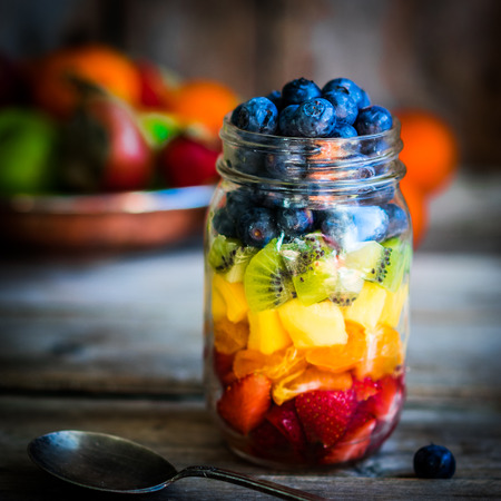 Colorful fruit salad in a jar on rustic wooden background Stockfoto