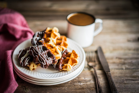 Belgian waffles with chocolate on rustic wooden background