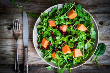 rocket lettuce: Fresh arugula and spinach salad with pumpkin on rustic background