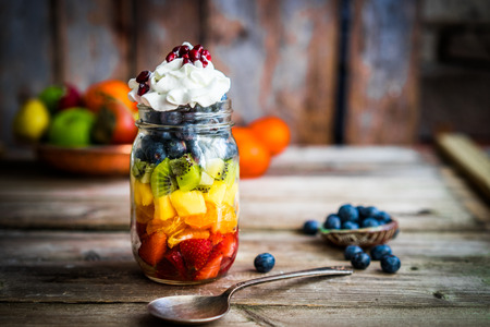fruit salad: Colorful fruit salad in a jar on rustic wooden background Stock Photo