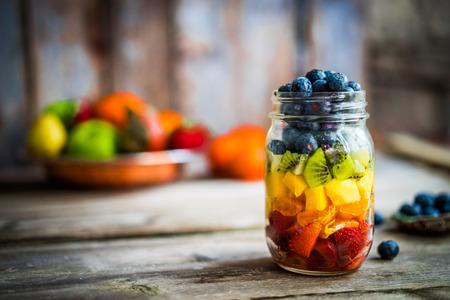 소박한 나무 배경에 항아리에 다채로운 과일 샐러드 스톡 콘텐츠