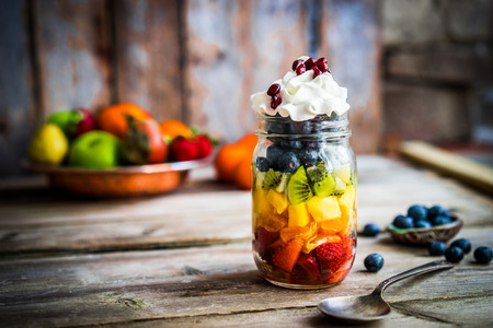 of fruit: Colorful fruit salad in a jar on rustic wooden background Stock Photo