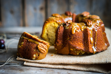 Homemade autumn cake with nuts and caramel on wooden background