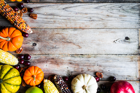 organic background: Pumpkins,corn,apples,nuts and cranberries on wooden background