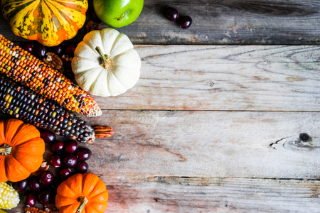 Pumpkins,corn,apples,nuts and cranberries on wooden background