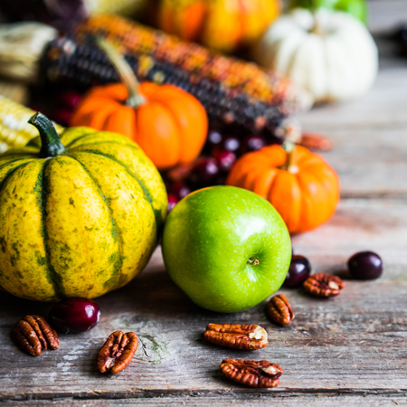 autumn food: Pumpkins,corn,apples,nuts and cranberries on wooden background