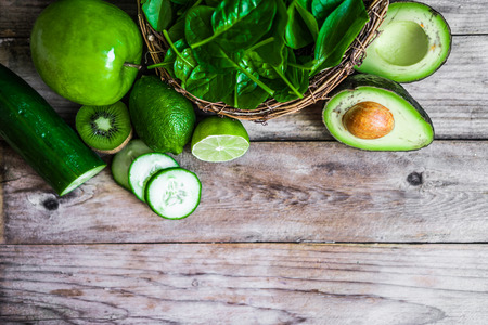 Mix of green fruits and vegetables on rustic wooden background
