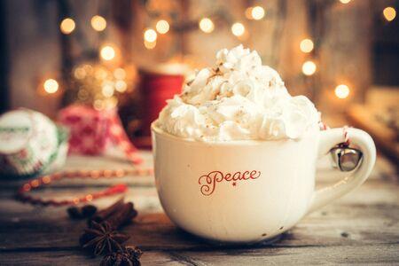 소박한 나무 배경에 휘저어 진 크림과 함께 크리스마스 잔에 뜨거운 코코아