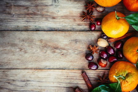 Tangerines with nuts,cranberries and cinnamon on rustic wooden background