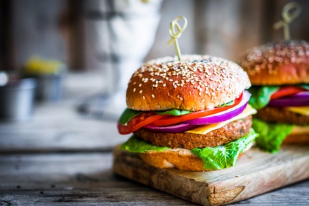 gourmet burger: Homemade burgers on rustic wooden background