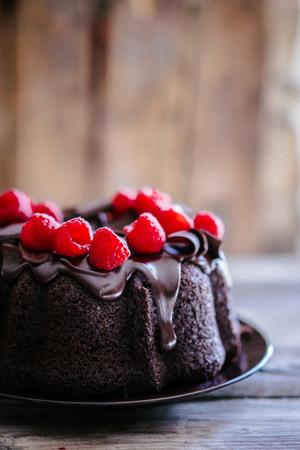 소박한 나무 배경에 라스베리와 초콜릿 케이크