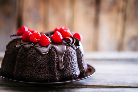 Chocolate cake with raspberries on rustic wooden background
