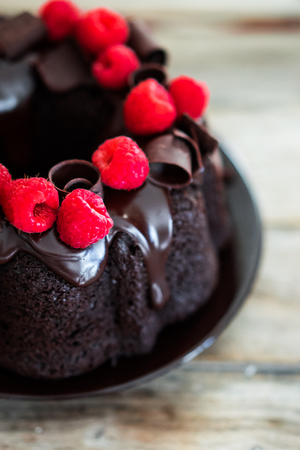 chocolate cakes: Chocolate cake with raspberries on rustic wooden background