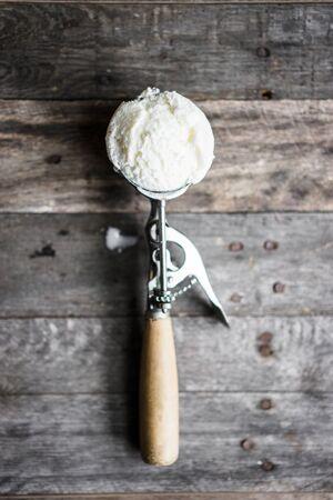 rich flavor: Scoop of vanilla ice-cream on rustic wooden background