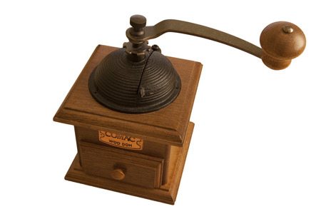 Vintage rustic wooden coffee grinder with a manual mechanism and large handle above a wooden box and drawer to grind fresh roasted coffee beans for a gourmet cup of aromatic espresso, on white photo