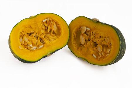 pips: Verse groene pompoen in tweeën gesneden om de voedzame pitten en oranje vruchtvlees, een traditionele groente voor Thanksgiving, geïsoleerd op wit weer te geven Stockfoto