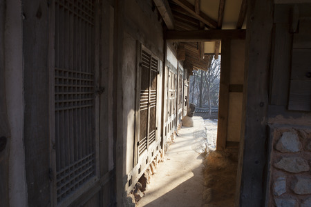 hinged: View down a narrow passageway looking towards bright sunlight in a traditional Korean folk village with a series of hinged doors in the walls leading to homes