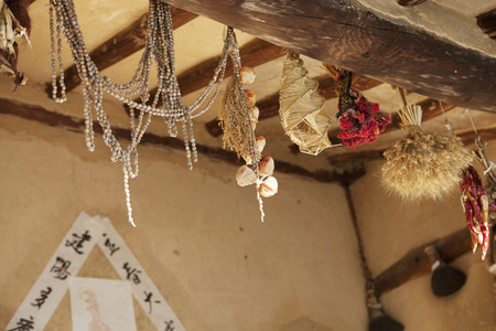 rafter: Traditional handicrafts in a Korean folk village made from a variety of natural materials including, grasses, straw and rope hanging from an interior roof rafter in a building