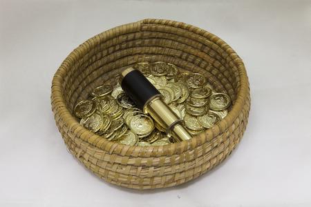 bounty: Pila de monedas de oro en una cesta con aa telescopio de bronce de �poca conceptual de una abundancia de monedas de oro a trav�s de la pirater�a, un tesoro, la inversi�n, la fortuna o de ahorros Foto de archivo