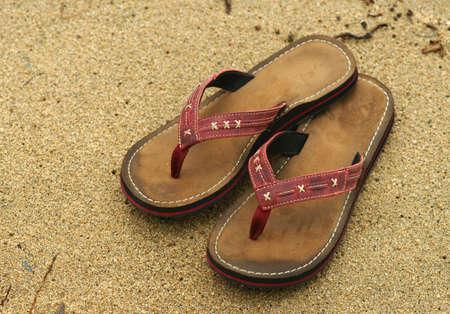 flops: Flip flops left on a sandy beach.