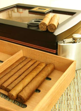 Cigars, cigar humidor, hip flask. Close up.