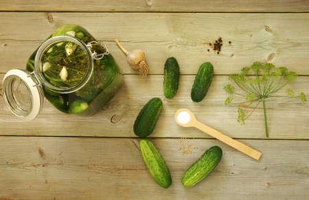 PICKLES: Cotos hechos en casa. Preparación de pepinos encurtidos. Pepinos frescos en un tarro y los ingredientes en una mesa