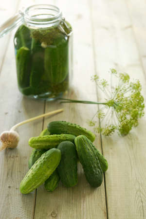 gherkins: Homemade preserves. Preparation of pickled cucumbers. Fresh cucumbers in a jar and ingredients on a table Stock Photo