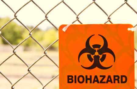 Biohazard sign attached to a chain link fence Stock Photo - 20198159
