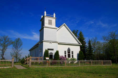 american field service: Restored church with a gorgeous blue sky background  Port Sanilac Historical Village  Port Sanilac, Michigan  Stock Photo