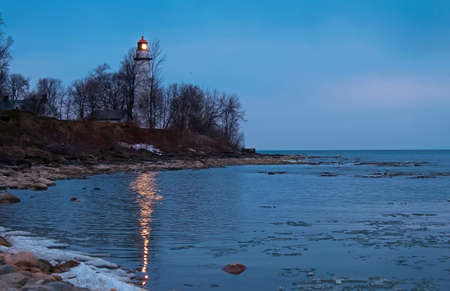 Point Aux Barques Lighthouse beacon reflecting off the icy waters of Lake Huron  Lighthouse County Park  Port Hope, Michigan  photo