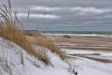 Sand dune blanketed in snow with a storm tossed Lake Huron in the background  Port Crescent State Park  Port Austin, Michigan