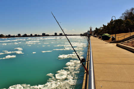 huron: Fishing for steelhead along the St. Clair River as blocks of ice flow downriver. Stock Photo