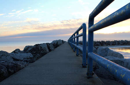 huron: Sunrise stroll  Serene sunrise along the Lake Huron shoreline with the tranquil water of the Great Lake in the backgroud  Lexington State Harbor  Lexington, Michigan