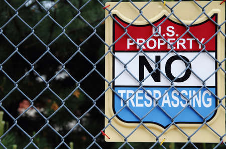 Keep out  U S  Property, No Trespassing Sign attached to a chain link fence  photo