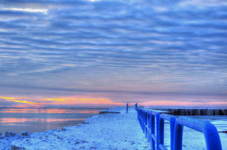 frozen lake: The End of the Earth  Sunrise on the horizon over an icy Lake Huron  Port Sanilac Harbor  Port Sanilac, Michigan  Stock Photo