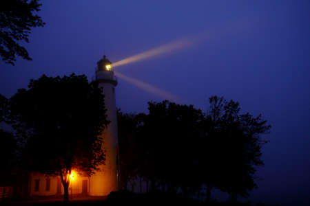 Point Aux Barques Lighthouse twin beams light up the foggy Lake Huron shoreline  Warning mariners of the hidden danges that lie beneath the treacherous Great Lakes waters  Lighthouse County Park  Port Hope, Michigan  Stock Photo