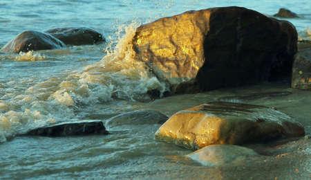 huron: The Wave  Waves splashing over the golden rocks on the Lake Huron shoreline