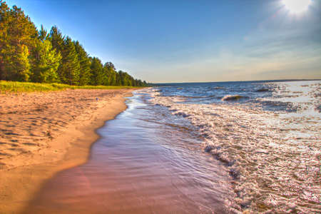 The sun is shining as waves crash on a golden beach  Whitefish Bay Scenic Byway  Brimley, Michigan