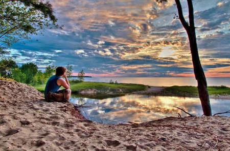 Eenzame wandelaar op het strand kijken naar de zonsondergang Port Crescent State Park Port Austin, Michigan Stockfoto