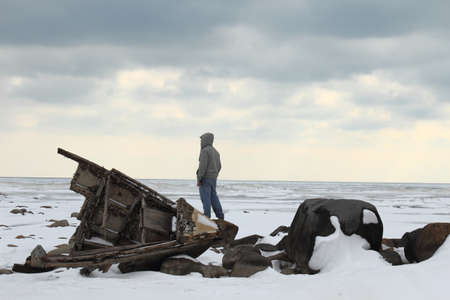 Single male looking over a desolate Lake Huron with a shipwreck in the foreground  Lexington County Park  Lexington, Michigan photo
