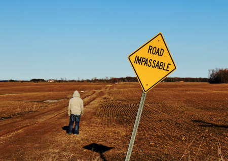 the desolate: Road impassable sign with teenager bravely crossing into the unknown  Stock Photo