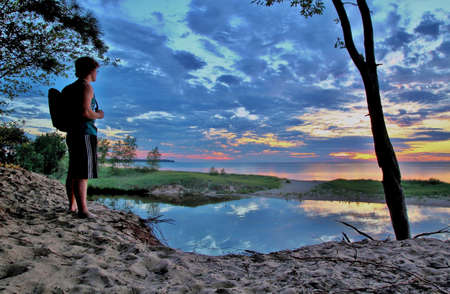 Teenaged male hiker taking in the Great Lakes Sunset  Port Crescent State Park  Port Austin, Michigan  Stock Photo